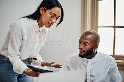 Buy stock photo Shot of a young businessman and businesswoman using a digital tablet during a meeting in a modern office