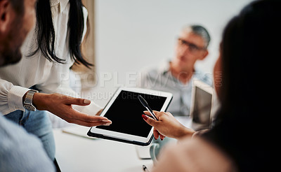 Buy stock photo Shot of a group of businesspeople using a digital tablet during a meeting in a modern office