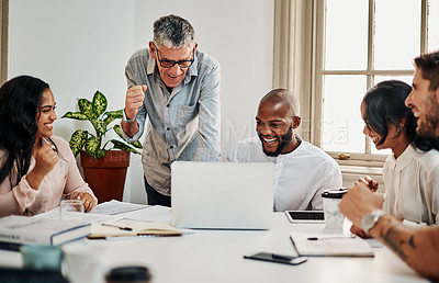Buy stock photo Shot of a group of businesspeople cheering while using a laptop during a meeting in a modern office