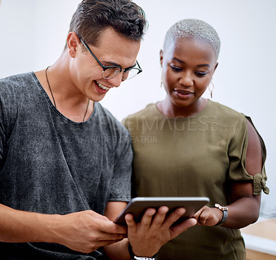 Buy stock photo Shot of two businesspeople working together on a digital tablet in an office