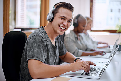 Buy stock photo Portrait of a young businessman wearing headphones while working on a laptop in an office