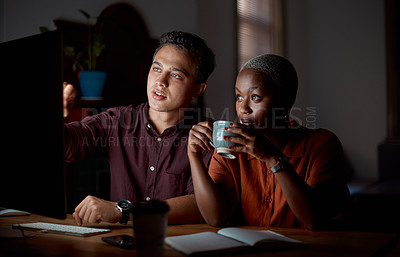 Buy stock photo Shot of two businesspeople working on a computer in an office at night