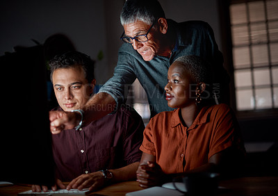 Buy stock photo Shot of a group of businesspeople working on a computer in an office at night