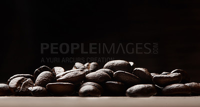 Buy stock photo Still life shot of coffee beans on a wooden countertop against a black background