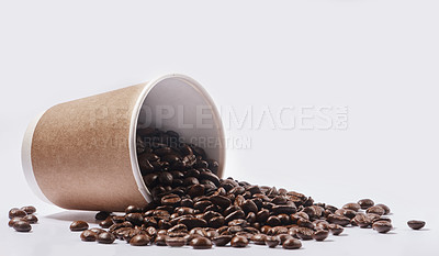 Buy stock photo Studio shot of a tipped over paper cup filled with coffee beans against a white background