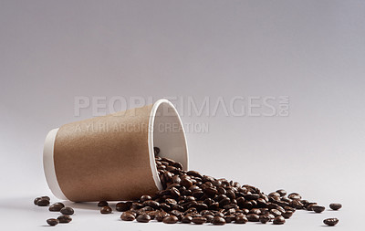 Buy stock photo Studio shot of a tipped over paper cup filled with coffee beans against a grey background