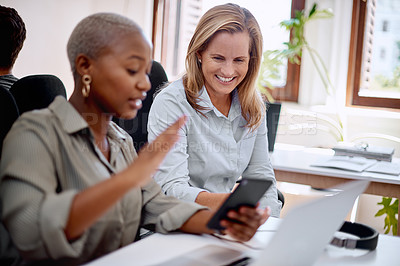 Buy stock photo Shot of two businesswomen looking at something on a cellphone in an office