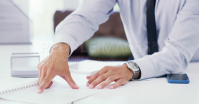 Buy stock photo Closeup shot of an unrecognisable businessman going through paperwork in an office