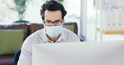 Buy stock photo Shot of a young businessman wearing a mask while working on a computer in an office