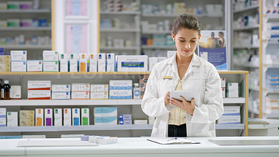 Buy stock photo Shot of an attractive young female pharmacist using a digital tablet while standing behind the counter in a chemist
