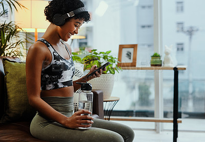 Buy stock photo Shot of a young woman using a cellphone while exercising at home