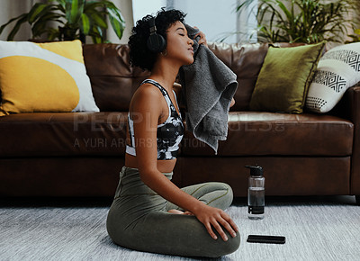 Buy stock photo Shot of a young woman wiping her face with a towel while exercising at home