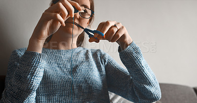 Buy stock photo Cropped shot of a woman cutting off a piece of thread while sitting at home