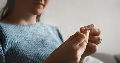 Buy stock photo Cropped shot of an unrecognizable woman trying to get thread a needle