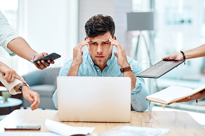 Buy stock photo Shot of a young businessman looking stressed out in a demanding office environment