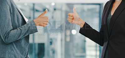 Buy stock photo Cropped shot of two businesswomen showing thumbs up in a modern office