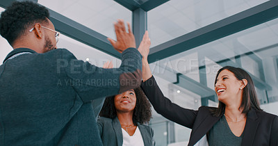 Buy stock photo Shot of a group of young businesspeople giving each other high five in a modern office