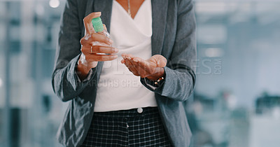 Buy stock photo Cropped shot of a businesswoman using hand sanitiser in a modern office