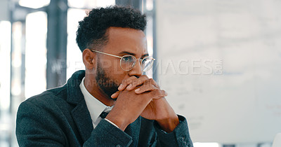 Buy stock photo Shot of a young businessman looking thoughtful in a modern office