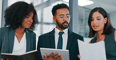 Buy stock photo Shot of a group of young businesspeople using a digital tablet during a discussion in a modern office