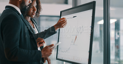 Buy stock photo Shot of a young businessman and businesswoman using an interactive whiteboard to analyse data in a modern office