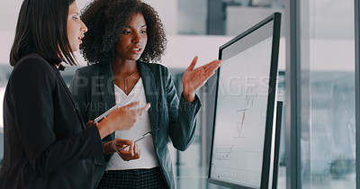Buy stock photo Shot of two young businesswomen using an interactive whiteboard to analyse data in a modern office