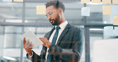 Buy stock photo Shot of a young businessman using a digital tablet during a brainstorming session in a modern office