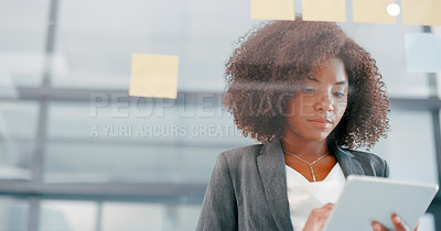 Buy stock photo Shot of a young businesswoman using a digital tablet during a brainstorming session in a modern office