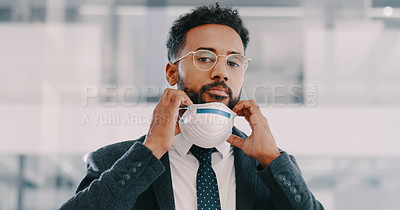 Buy stock photo Shot of a young businessman wearing a protective mask in a modern office