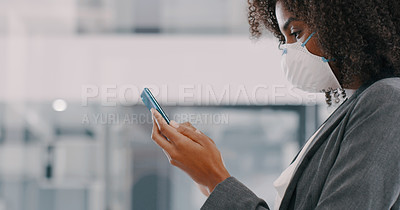 Buy stock photo Shot of a young businesswoman wearing a mask and using a smartphone in a modern office