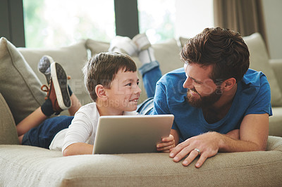 Buy stock photo Shot of an adorable little boy using a digital tablet with his father on the sofa at home