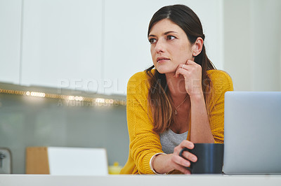 Buy stock photo Shot of a young woman having a cup of coffee and using a laptop in her kitchen at home