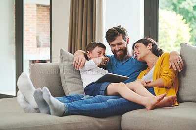 Buy stock photo Shot of an adorable little boy using a digital tablet with his parents on the sofa at home