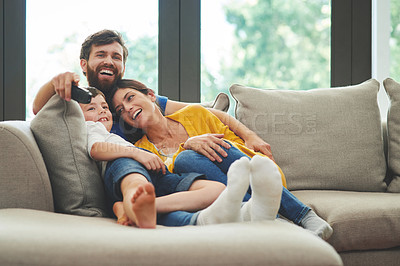 Buy stock photo Shot of a happy family watching television on the sofa at home