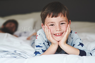Buy stock photo Portrait of an adorable little boy relaxing on the bed with his father in the background