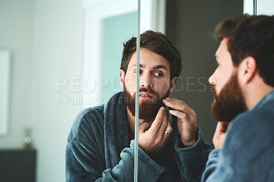 Buy stock photo Shot of a handsome young man inspecting his face in the bathroom mirror