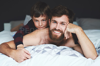 Buy stock photo Shot of an adorable little boy relaxing with his father on the bed in the morning at home