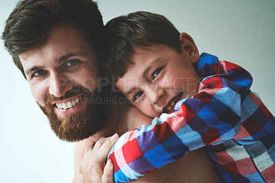 Buy stock photo Shot of an adorable little boy hugging his father in the morning at home