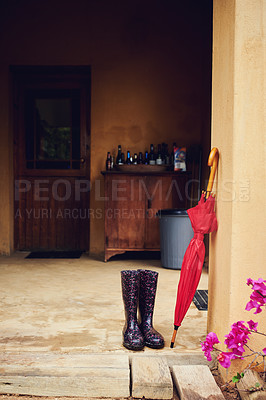 Buy stock photo Shot of two rain boots and an umbrella in the backyard at home