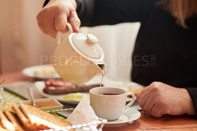 Buy stock photo Closeup shot of an unrecognisable woman pouring tea into a cup at home