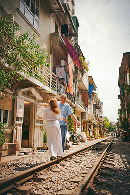 Buy stock photo Shot of a happy couple sharing a romantic moment on the train tracks in the streets of Vietnam