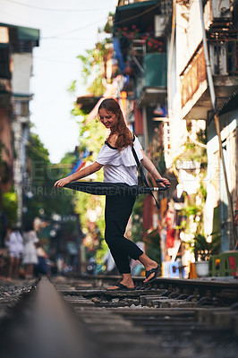 Buy stock photo Shot of a young woman holding an umbrella while exploring a foreign city on a sunny day