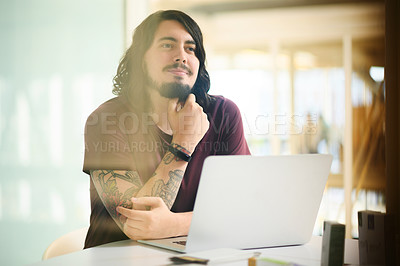 Buy stock photo Shot of a young businessman looking thoughtful while working on a laptop in an office