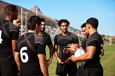 Buy stock photo Shot of a group of young rugby players having a discussion on the field