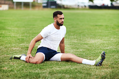 Buy stock photo Shot of a young man doing stretches on a rugby field