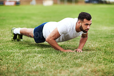 Buy stock photo Shot of a young man doing push ups on a rugby field