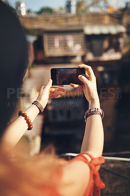 Buy stock photo Cropped shot of a young woman taking pictures on her cellphone while out in the city