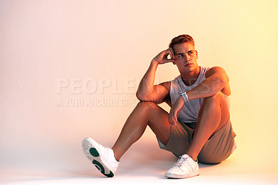 Buy stock photo Studio shot of a handsome young male athlete looking thoughtful against a multi-coloured background
