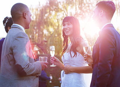 Buy stock photo Shot of a happy young couple having champagne with their guests after getting married