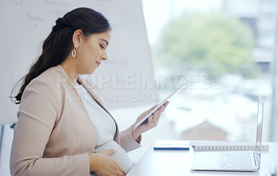 Buy stock photo Cropped shot of a pregnant businesswoman using a digital tablet while sitting at her desk
